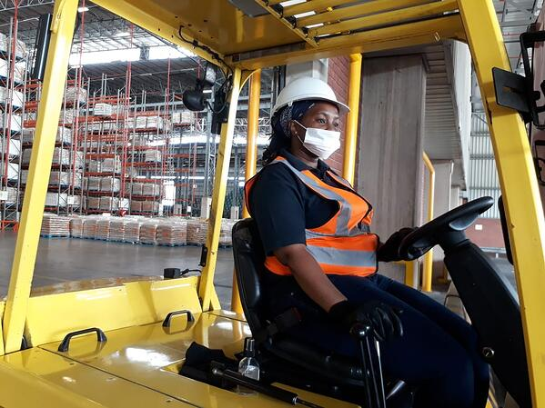 South African woman working as an essential worker in a warehouse wearing a mask and gloves due to COVID-19